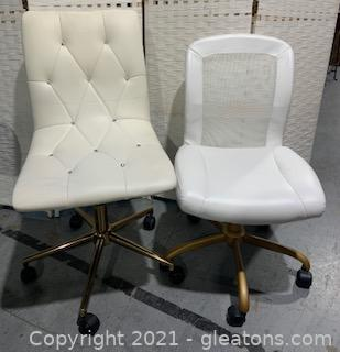 Two Mismatched White Wheeled Swivel Chairs with Gold Accent