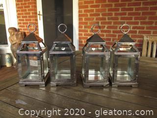 4 Metal and Glass Votive Candle Lanterns Each on is 8 1/2 inches tall and 3 1/2 square at the bottom / Hinged door that opens / Glass on 4 sides and open at the top on four sides
