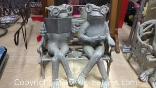 TWO CONCRETE FROGS SITTING ON A BENCH